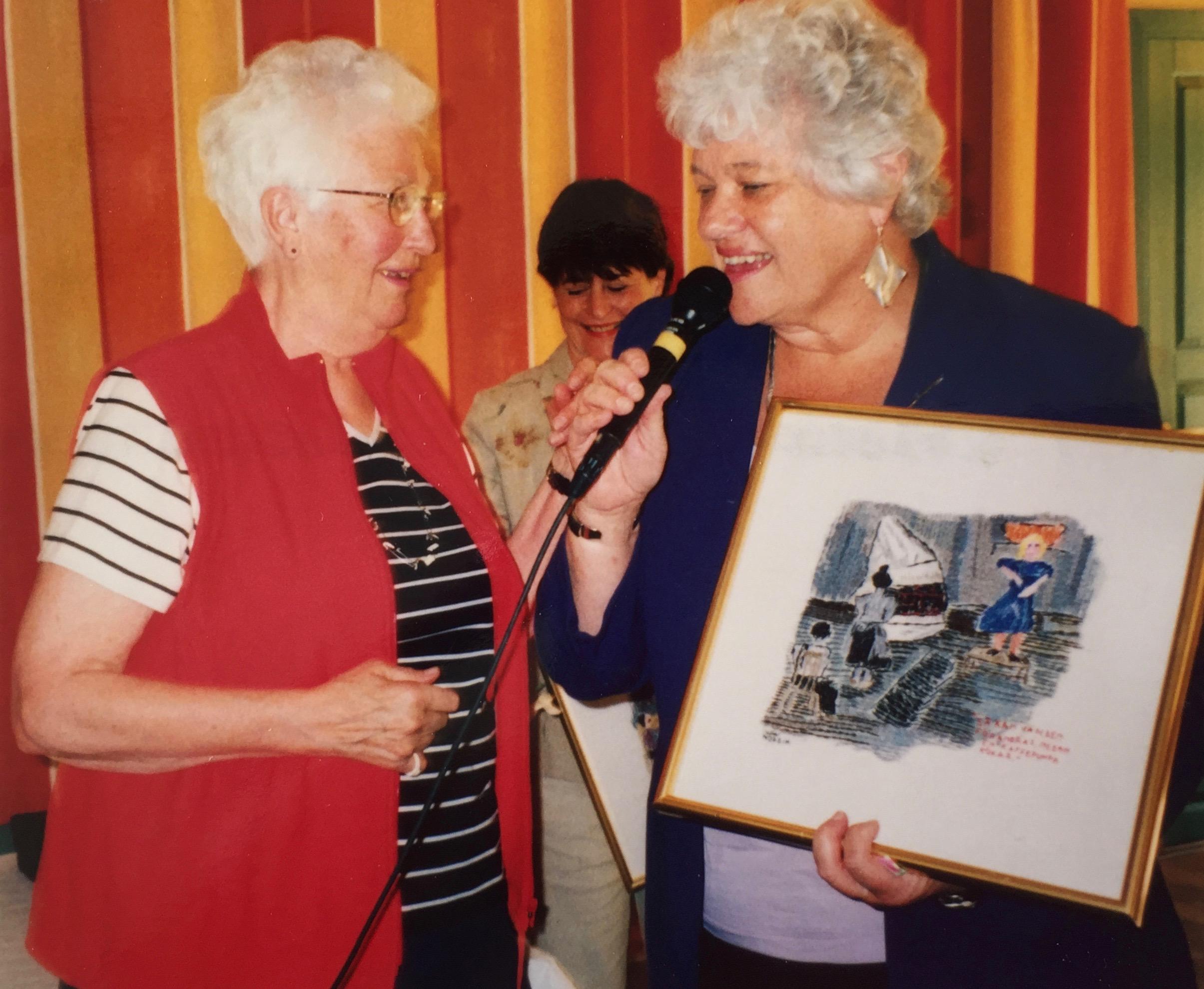 Ulla Nordin, som ställde ut på Lilla Björka året innan, överlämnar ett av sina broderade konstverk till stiftelsens ordförande Charlotte Branting