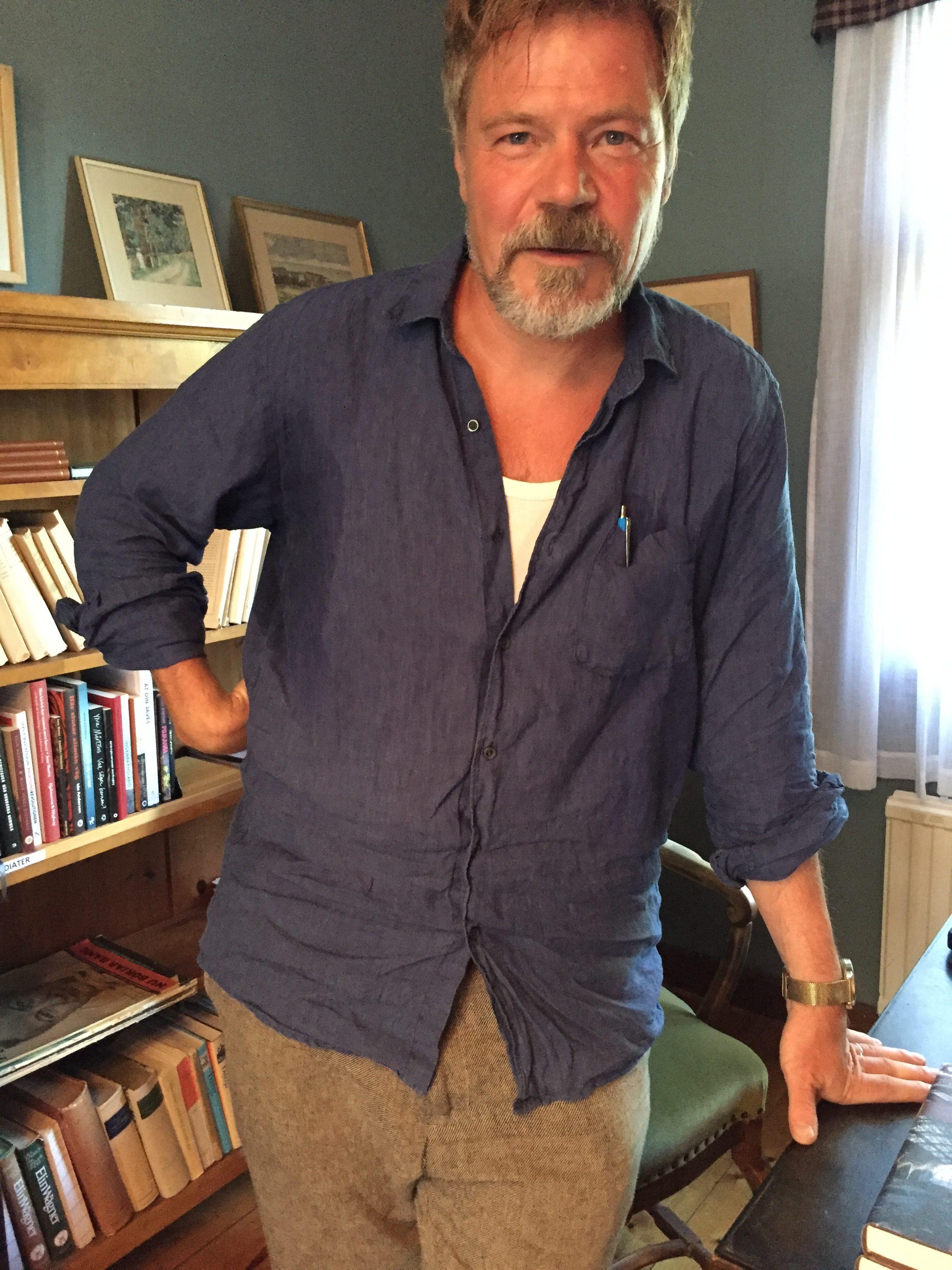 Kristoffer Leandoer framför bokhyllan med lejontassar i vardagsrummet.
