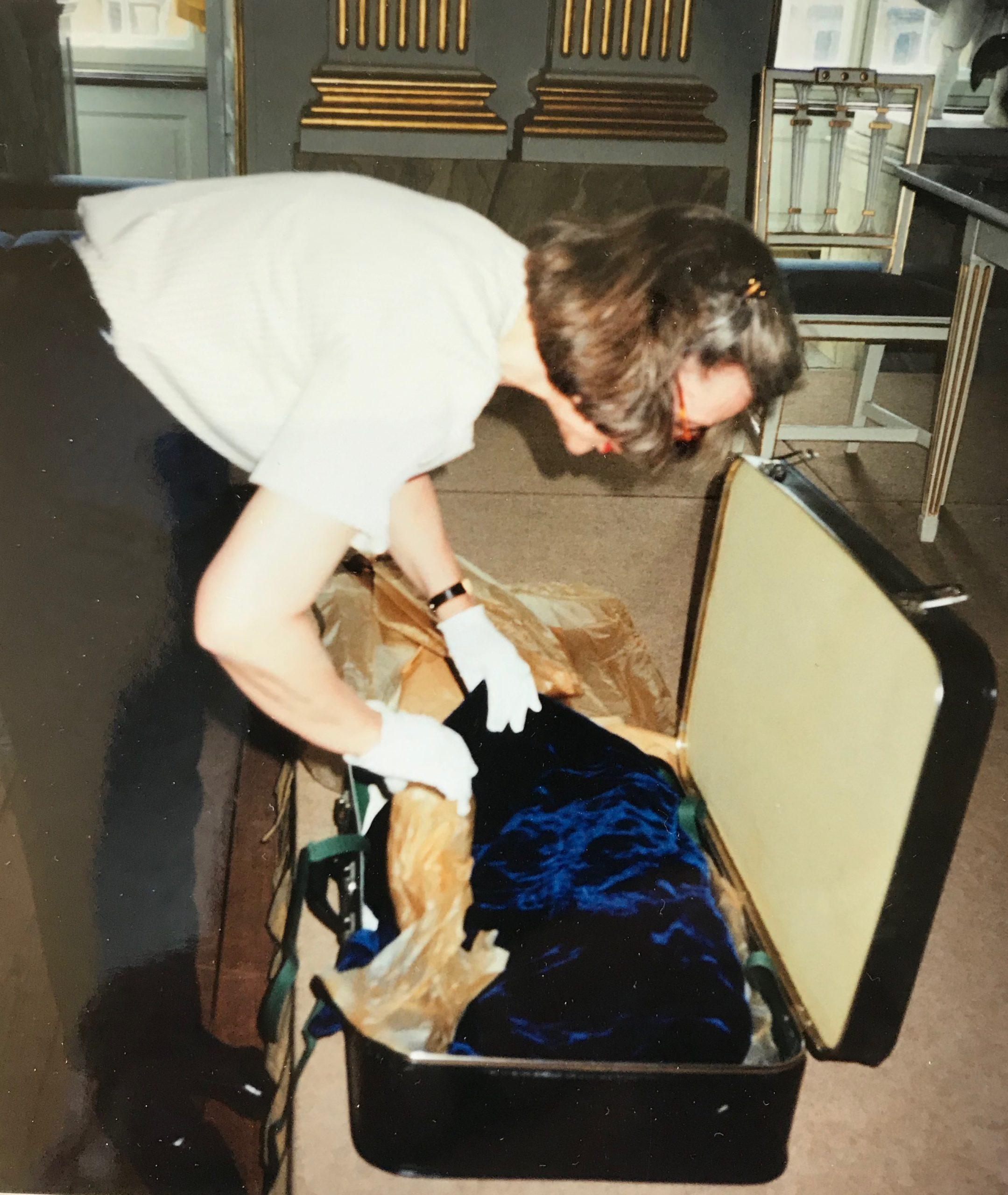 Kopian av Elins klänning packas upp av antikvarie med handskar.